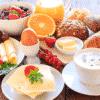 Afbeelding van het Ontbijt Heerlijk ontbijt beschikbaar voor ontbijtservice. Op de afbeelding is onder andere afgebeld vers fruit, croissants en vers gebakken broodjes.