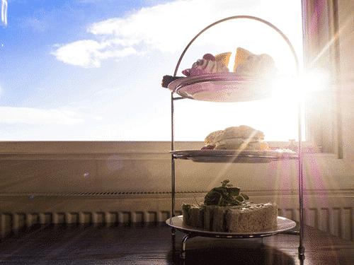 Afbeelding van de Zomer High Tea. Op de afbeelding zijn afgebeeld verschillende lekkernijen die refereren naar de zomer zoals luxe broodjes.